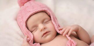 Bebe dormindo e touca rosa